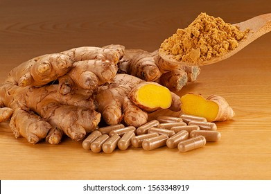 Ginger root Organic. Ginger root Biologically on a wooden plate with a wooden spoon filled with ginger powder and capsules with ginger powder.