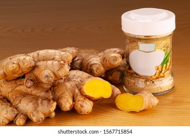 Ginger root Organic. Ginger root Biologically on a wooden plate with a jar filled with ginger powder.