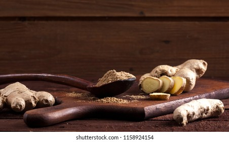 Ginger root and ginger powder in spoon on wooden background