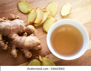 Ginger root and slices with a cup of ginger tea on wood background. Soft warm light effect added.