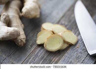 Ginger root and ginger slices with knife on cutting board.