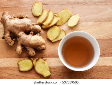 Ginger root and slices with white cup of ginger tea on wood background.