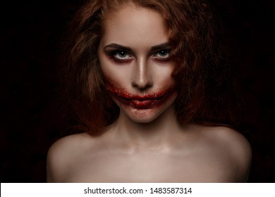 Ginger scary girl with cutted mouth looking her blue eyes to the camera. Halloween makeup