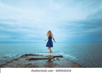 Ginger tatooed girl in blue dress and sea
