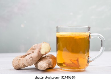 Ginger tea in a cup on wooden background