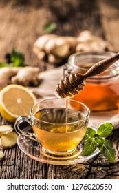 Ginger tea honey lemon and mint leaves on wooden table.