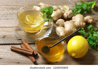 Ginger tea with lemon in glass cup, ginger root, honey in bowl, cinnamon and mint on rustic wooden background.