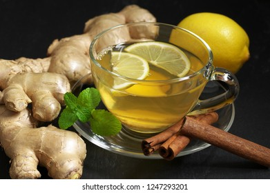 Ginger tea with lemon in glass cup, ginger root, cinnamon and mint on slate against black background.