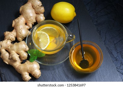 Ginger tea with lemon in glass cup, ginger root, honey and mint on slate against black background.