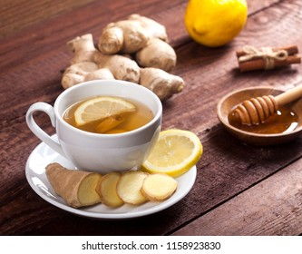 Ginger tea with lemon honey and cinnamon on wooden background