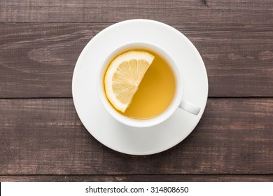 Ginger tea with lemon on the wooden background.