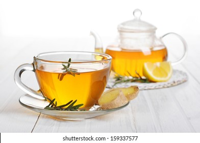 Ginger tea with lemon and rosemary in glass cup closeup.
