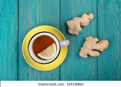 Ginger tea in a vintage cup on wooden background