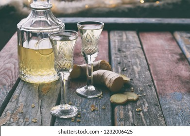 Ginger tincture or ale on wooden background. Spice yellow liqueur in a glass. Homemade Alcohol drink. Rustic style.