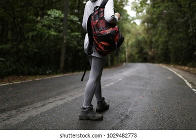 Ginger travel hiker women walking on the road alone,with backpack,hiker shoes,coat,mountain view,forest road,jungle road,expedition tour,guide,spring season,raincoat,map,destination,shoes,equipment