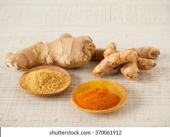 Ginger , turmeric powder and root on a table