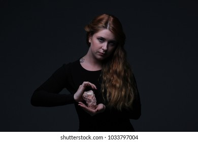 Ginger woman in black dress with stone on dark background
