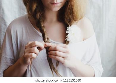 Ginger woman braids her hair