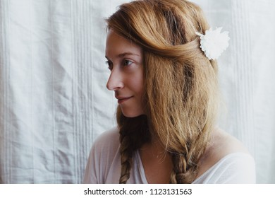Ginger woman with braids and white chrysanthemum in her hair