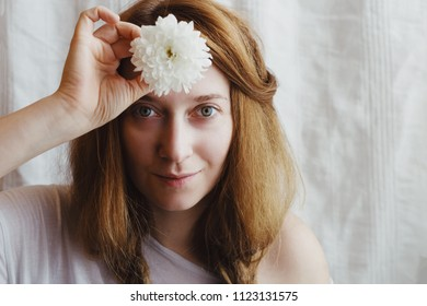Ginger woman with braids and white chrysanthemum in her hand