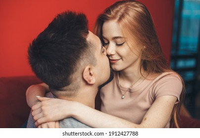 Ginger woman embracing her lover and kissing while lying on a couch
