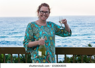 Ginger woman in her forties by the seaside, drinking champagne