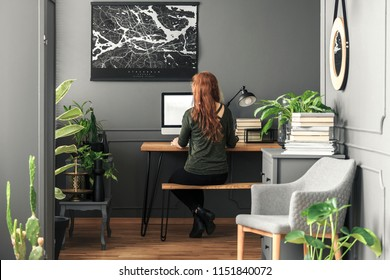 Ginger woman sitting by a wooden hairpin desk with mockup computer in real photo of dark grey living room interior