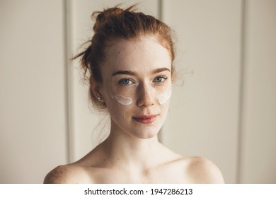 Ginger woman wearing hydrogel eye patches looking at camera with bare shoulders