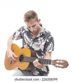 ginger young man with hawaiian shirt playing the guitar