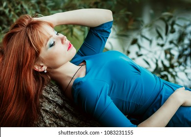 ginger young model in a blue long dress lying down on a tree in a park, outdoors among trees, green background with trees, posing for camers, calm emotions