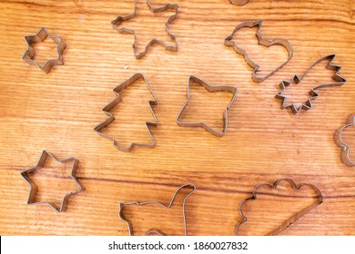 Gingerbread aluminum cookie cutters on wooden board top view