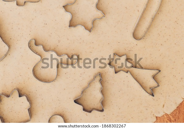 Gingerbread aromatic and spiced dough for Christmas cookies with different shape metal cookie cutters.Preparing Christmas cookies using cookie cutters. Close up view. Baking concept. Top view.