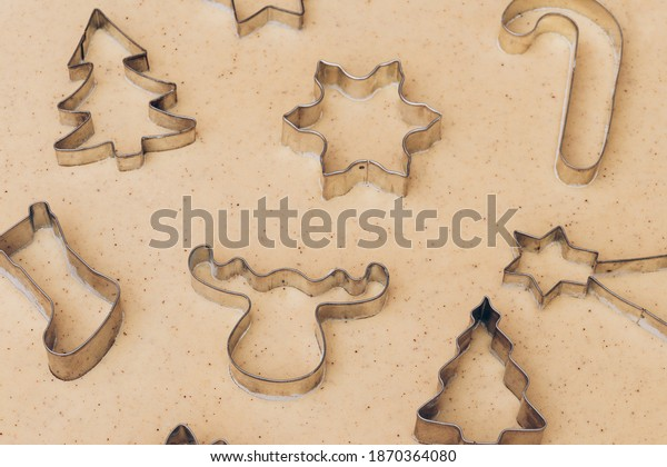 Gingerbread aromatic and spiced dough for Christmas cookies with different shape metal cookie cutters.Preparing Christmas cookies using cookie cutters. Close up view. Baking concept. Selective focus.