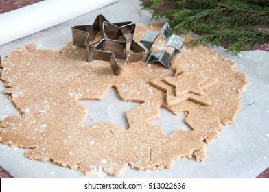 Gingerbread batter (dough) on parchment paper with star cutters.