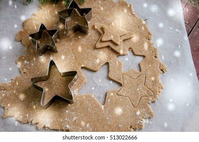 Gingerbread batter (dough) on parchment paper with star cutters. Top view. Wooden background. Toned.