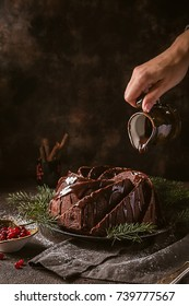 Gingerbread Bundt Cake for Christmas with lingonberry and christmas decorations over dark background