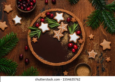 Gingerbread chocolate tart decorated with rosemary, cranberries and gingerbread stars. Christmas dessert. Top view