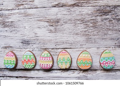gingerbread cookie in the form of color eggs on dark wooden background. Happy Easter card. Bright biscuits. Treats for children. copy space