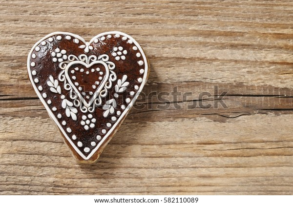 Gingerbread cookie in heart shape on a wooden background, copy space.
