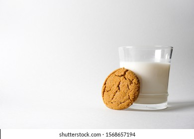A gingerbread cookie leans up against a glass of cold milk on a white background with copy space on the left