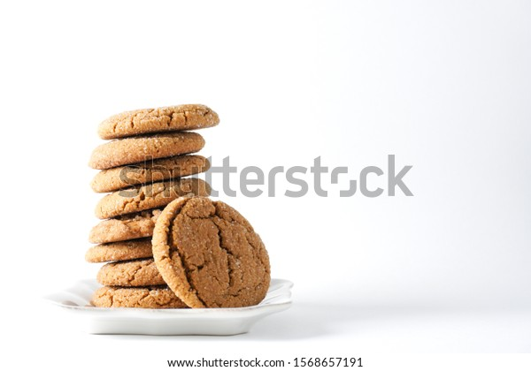 A gingerbread cookie leans on a stack on cookies on a white plate isolated on a white background; copy space on right