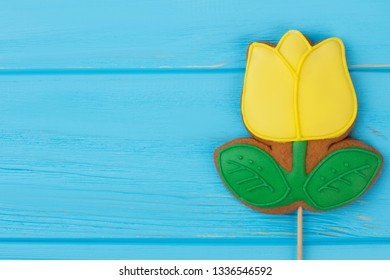 Gingerbread cookie in a shape of tulip. Yellow frosted biscuit in a form of spring flower on blue wooden background, copy space. Easter or Mothers Day concept.