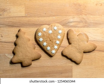Gingerbread cookies of Christmas tree, angel and heart-shape on wooden board