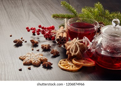 Gingerbread cookies, fruit tea and fir tree branches on a wooden black background.  Christmas and New Year treat.