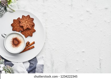 Gingerbread cookies with hot cocoa drink or eggnog on a serving plate over white marble table covered with snow. Top view of traditional Christmas gingerbread cookies. Christmas breakfast concept.