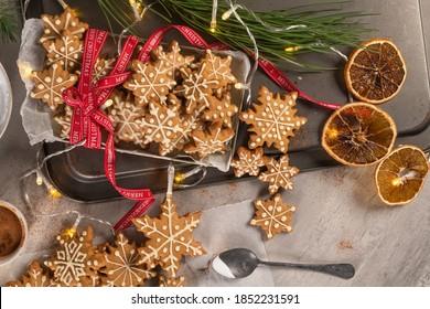 Lebkuchenkochen mit Eis auf dem Countertop mit festlichem Licht. Weihnachtskekse Schneeflocken verziert mit Zuckerfrost. Weihnachtsferien-Tradition und Adventszeit