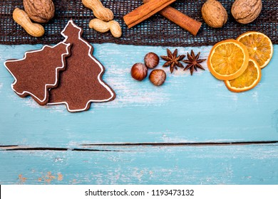 Gingerbread cookies with nuts, winter spices and orange slices on wooden table, copyspace