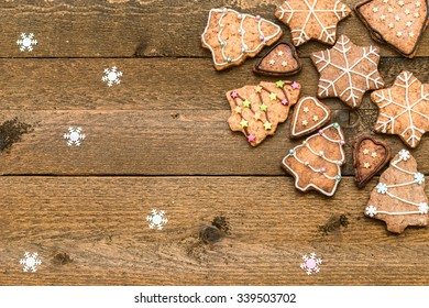 Gingerbread cookies on wooden background with snowflakes with space for your text
