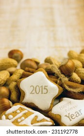 gingerbread cookies on wooden table with nuts and cinnamon for 2015 - Happy New Year