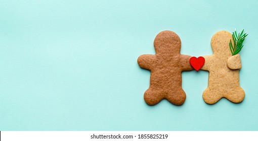 Gingerbread cookies in the shape of man and woman holding hands with fir branch and red wooden heart. Interracial couple in love. Christmas love concept. 14 february. Blue background. Copy space.